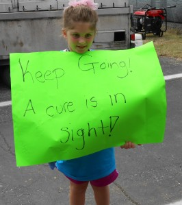 Brianna enthusiastically marches around the area carrying a sign with the positive news that a cure for MS is in sight. Children can learn the value and positive benefits of volunteering at an early age.