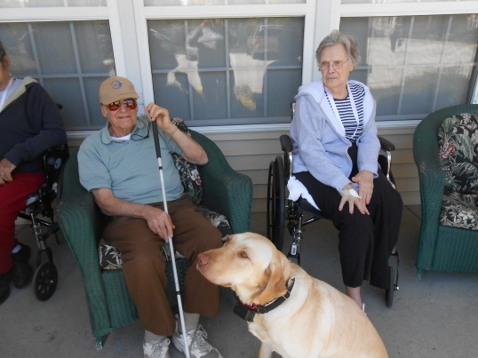 Ms. Joanne, Adam, and Gunner, the community dog, at Juniper Village