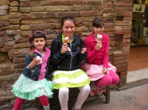 Three friends in colorful outfits enjoy gelato in San Gimignano.