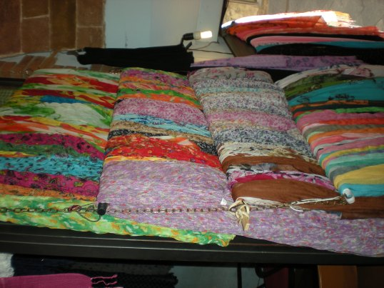 Multicoloured scarves for sale in a tiny upstairs shop in Siena.