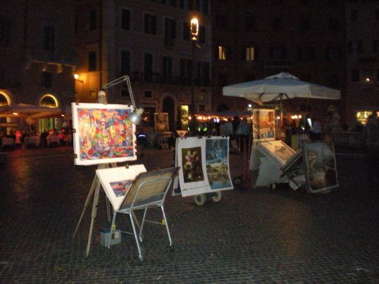 Colorful atmosphere and multicolored painting in Piazza Navona at night.