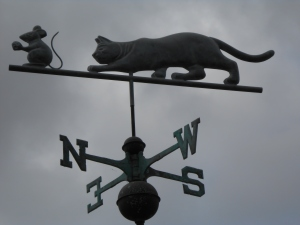 Cat chases mouse on top of a weather vane. San Diego, CA, Olde Town