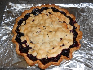 Blueberry pie cooling on shiny tin foil.